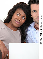 Mixed couple with laptop