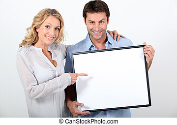 Couple pointing at blank board