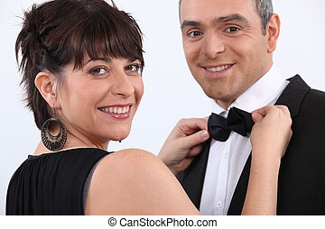 Woman putting bow tie to man