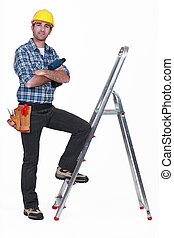 Portrait of a tradesman with his foot propped on a...