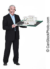 Architect wearing head-set and holding model housing
