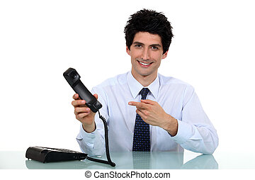 Cheerful employee pointing at telephone