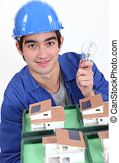 young craftsman holding a bulb and an architectural model of houses
