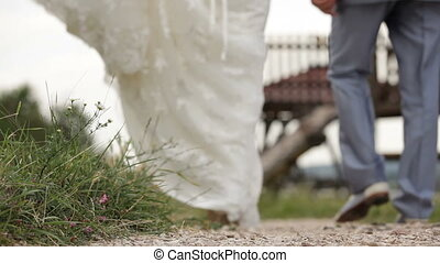 Newly weds walking hand in hand - Newly weds walking down a...