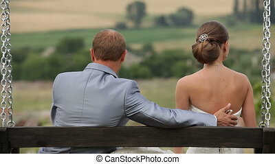 Newly weds embracing each other - Newly weds seating on a...