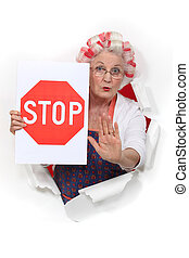 An old lady with a stop sign