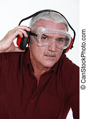Senior man with goggles and protective headphones