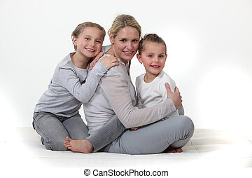 mother embracing her two little girls