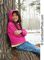 Child sitting under tree in winter