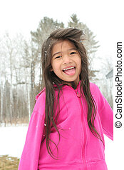 Child sticking out tongue while playing outdoors in winter