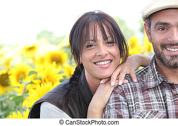Farmer and wife stood in field of sunflowers
