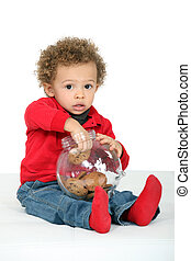 Child taking a cookie from a jar