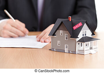 Businessman signs contract behind household architectural model