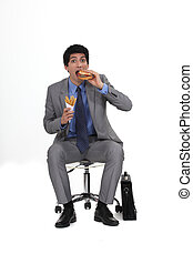 Businessman sat eating burger and French fries