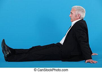 Profile of senior businessman sat on the floor
