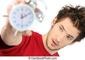 A frazzled man holding an alarm clock