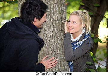 Couple hiding either side of tree