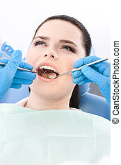 Dentist examines the dentes of the patient on the dentist's...
