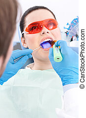 Dentist uses photopolymer lamp to treat teeth - Dentist uses...