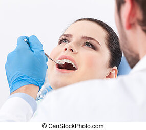 Dentist examines teeth of the patient on the dentists chair