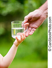 Little girl taking a glass of water from grandpa - Senior...