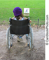 Young girl in wheelchair from back - A young girl in a...