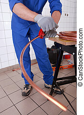 Plumber cutting copper pipe