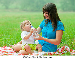 happy mother and daughter drinking clear water from bottle
