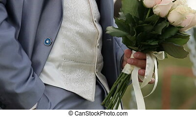 Groom with brides bouquet - Groom standing with brides...