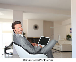 Businessman sat at home with laptop