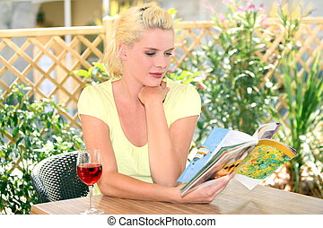 Woman reading with a glass of wine
