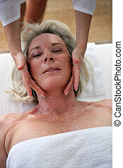 Grey-haired lady receiving face massage