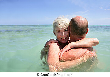 Middle-aged couple hugging in the sea