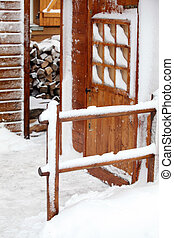 Snow covered logs and cabin