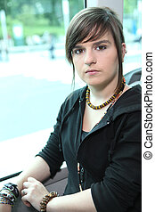Funky young woman sitting on a tram