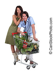Couple stood with trolley full of vegetables