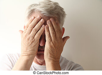 man covers his face - an older man hides his face in...