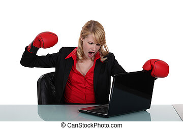 businesswoman hitting her laptop with a boxing glove