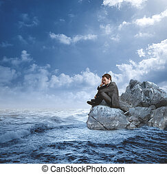 Businessman in crisis on the rocks
