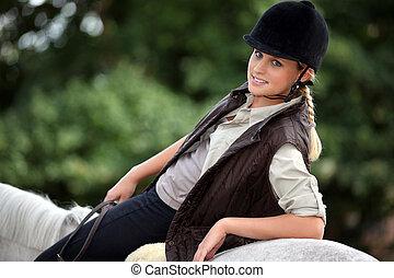 Blond teen riding her horse