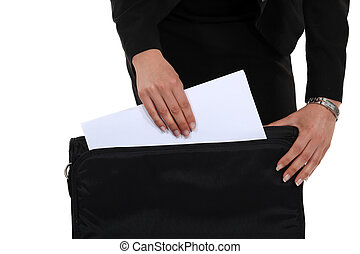 A businesswoman taking papers out of his briefcase.