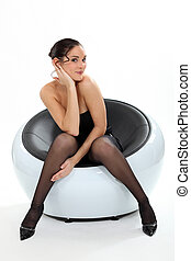 Sexy lady wearing a dress sat in an armchair