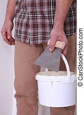 Man holding bucket of plaster and trowel