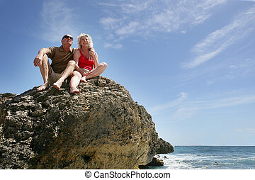 Senior couple sat on a rock by the sea