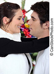 Couple hugging by their Christmas tree