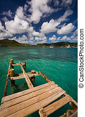 Antigua Explorations - Damaged dock over turquoise waters on...