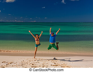 Anegada Explorations - Young couple jumping on white sand...