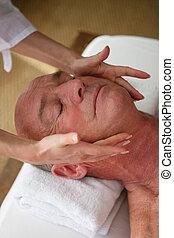 Elderly man receiving a head massage