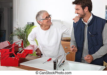 Plumber repairing sink for old lady