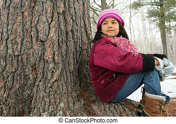 Nine year old girl sitting outdoors in winter - Nine year...